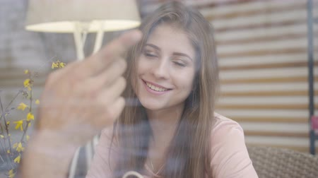way out : Close-up of beautiful smiling Caucasian girl looking out the window at the way pointed by male hand. Happy woman spending time with unrecognizable boyfriend in cafe on romantic date. Stock Footage