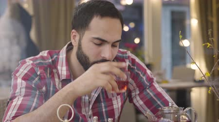 preocupações : Stressed Middle Eastern man drinking hot tea in cafe, looking away, shaking head and signing. Portrait of worried young handsome guy in restaurant thinking on problem solution. Anxiety, stress. Stock Footage