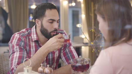 annoyance : Portrait of annoyed Middle Eastern man quarreling with Caucasian girlfriend in cafe. Irritated young handsome boyfriend arguing with brunette woman in restaurant. Communication problems, conflict. Stock Footage