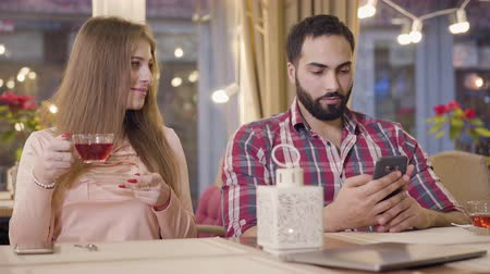caché : Portrait of cute Caucasian girl looking at boyfriend using smartphone and laughing. Middle Eastern man hiding phone and smiling. Joyful young couple resting in cafe. Relationship, joy, dating.