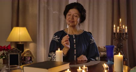mystik : Portrait of mature smiling woman blowing out match. Caucasian female fortune teller sitting at the table with lighting candles and cards. Magician, clairvoyant. Cinema 4k ProRes HQ. Dostupné videozáznamy