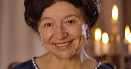 prévoyance : Close-up portrait of smiling mature Caucasian woman looking at camera and talking. Positive female magician posing at the background of lighting candles. Cinema 4k ProRes HQ. Vidéos Libres De Droits