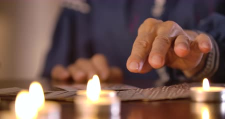 mystik : Extreme close-up of female Caucasian hands taking out cards from card deck lying on the table face down. Lighting candles standing at the foreground. Cinema 4k ProRes HQ.