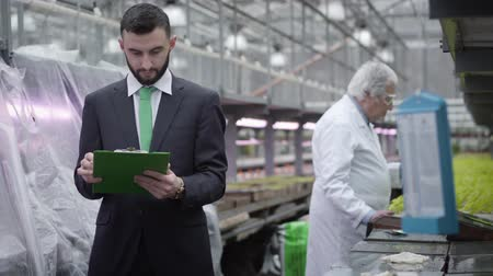 инспектор : Focus changes from young Caucasian inspector writing notes to mature biologist working with plants at the background. Handsome auditor checking production of organic foods in glasshouse. Agriculture.