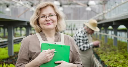jardinero : Close-up portrait of smiling senior Caucasian woman in eyeglasses looking at camera as male professional agronomist working at the background. Positive farmer posing in glasshouse. Cinema 4k ProRes HQ.