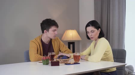 dizer : Middle shot of anxious Caucasian brunette woman telling bad news to teenage boy. Mother sharing problems with son sitting at the table indoors. Lifestyle, unity, trust, family. Vídeos