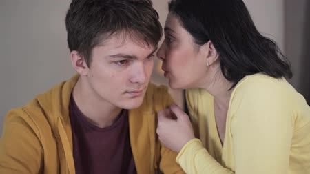 whispering : Close-up of brunette Caucasian woman whispering on ear of teenage boy. Mother sharing secrets with teen son. Trust, unity, reliance, lifestyle.