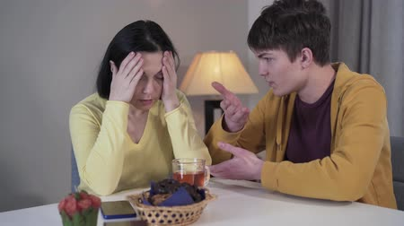 preocupações : Stressed Caucasian mother holding head in hands and looking at teenage son talking. Brunette woman worries about boy. Lifestyle, family, trouble, problem. Stock Footage