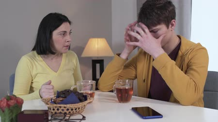 adolescência : Upset teenage Caucasian boy closing face with hands as his angry mother scolding him. Stressed brunette woman yelling at son for his behavior. Family, problem, stress.