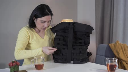 marijuana : Portrait of anxious young Caucasian mother finding cannabis in sons backpack. Worried woman taking out package of marijuana and thinking. Stress, drug addiction, adolescence.