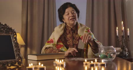 mystik : Camera moving from right to left around table with lighting candles and cards lying on it. Smiling mature Caucasian woman taking out three of cross and showing it on camera. Cinema 4k ProRes HQ.