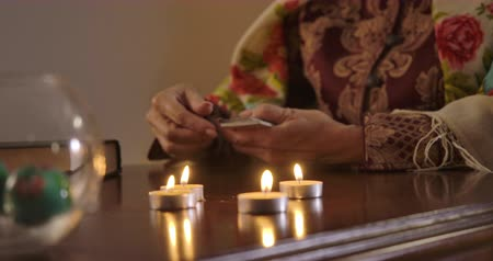 mystik : Close-up of female Caucasian elderly hand moving around candle light and taking out one card. Senior fortune teller putting jack of hearts on the table. Cinema 4k ProRes HQ.