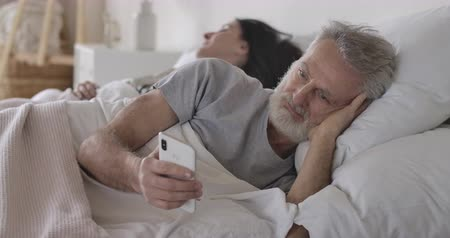 пробуждение : Close-up portrait of senior Caucasian man lying in bed and using smartphone as his wife sleeping at the background. Handsome mature man using modern technologies. Leisure, morning. Cinema 4k ProRes HQ.