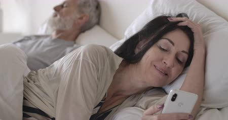ébredés : Close-up portrait of senior brunette Caucasian woman using smartphone lying in bed as husband sleeping at the background. Happy wife using social media. Lifestyle, joy, morning. Cinema 4k ProRes HQ. Stock mozgókép