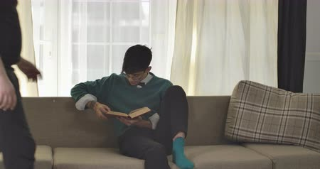 nerd : Annoying roommates coming to focused Caucasian boy reading and sitting down on couch on both sides. University students bullying nerd guy in eyeglasses. Cinema 4k ProRes HQ.