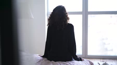 acorde : Young brunette woman sitting on bed and looking out the window. Back view of Caucasian girl in pajamas waking up in the morning.