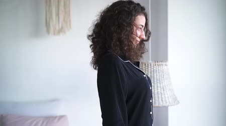 пробуждение : Pretty Caucasian woman falling back on bed. Side view of brunette curly-haired girl enjoying resting in bedroom or hotel room.