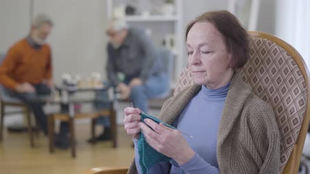 humanidade : Close-up portrait of mature Caucasian woman examining knitting. Old female retiree practicing hobby in nursing home.