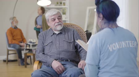 humanity : Portrait of smiling old Caucasian man listening to volunteer reading book. Young woman spending time with elderly male retiree in nursing home. Stock Footage