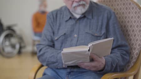 humanidade : Concentrated unrecognizable old Caucasian man reading literature in nursing home. Blurred male retiree in eyeglasses resting in nursing home. Focused on book.