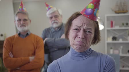 humanidade : Close-up face of crying old Caucasian woman in party hat. Upset elderly retiree celebrating birthday in nursing home. Blurred men standing at the background.
