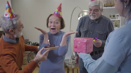 humanidade : Portrait of excited old Caucasian woman opening eyes as volunteer and elderly men bringing gift and birthday cake. Female retiree celebrating in nursing home.
