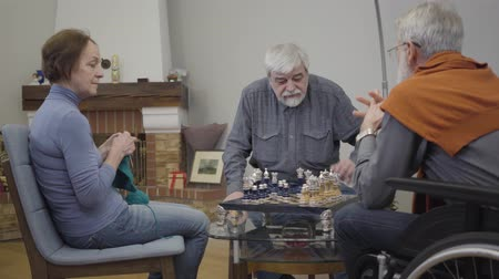 chlapík : Mature Caucasian woman knitting next to men playing chess in nursing home. Lifestyle of senior people after retirement. Dostupné videozáznamy