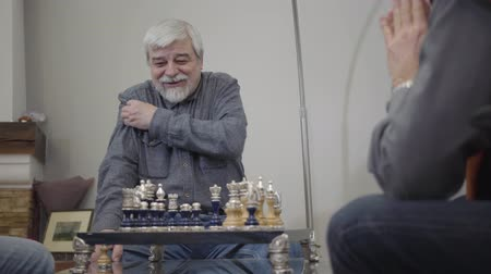 chlapík : Portrait of embarrassed old Caucasian man sitting in front of chess desk and smiling. Senior retiree playing with fellow in nursing home. Dostupné videozáznamy