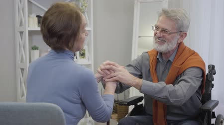 humanidade : Elderly handsome Caucasian man holding womans hands, talking and smiling. Happy senior retirees enjoying time together in nursing home. Stock Footage