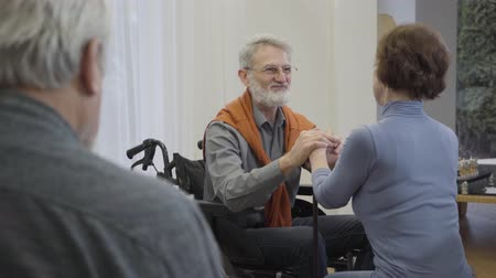 резидент : Graceful old Caucasian man in wheelchair holding hands of senior woman. Mature retiree in love flirting with female resident of nursing home. Lonely man reading at the foreground.