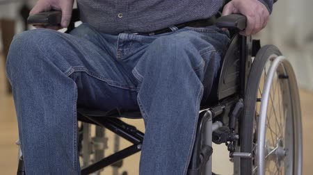 impaired : Unrecognizable Caucasian old man trying to stand up from wheelchair. Desperate disabled male retiree with paralyzed legs. Stock Footage