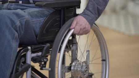 impaired : Close-up of male mature Caucasian hand rolling wheel of wheelchair. Unrecognizable disabled man leaving away to the left. Stock Footage