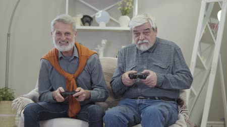 chlapík : Portrait of two cheerful Caucasian old men playing video game. Happy grey-haired retirees having fun in nursing home. Lifestyle, leisure. Dostupné videozáznamy