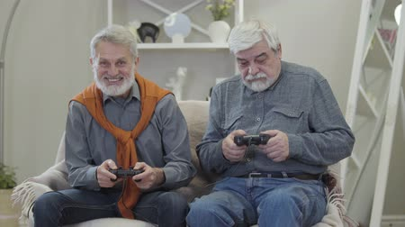 humanidade : Two happy old Caucasian men playing video game, giving five and smiling. Positive cheerful retirees having fun indoors.