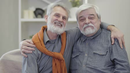 polegar : Portrait of two grey-haired Caucasian men talking at camera and showing thumbs up. Happy elderly retirees posing in nursing home. Vídeos