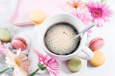 macarons : cup of Coffee With Colorful Flowers And Dessert On The Side