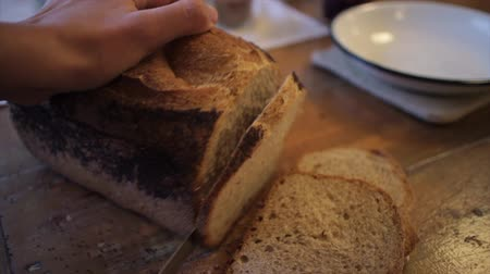 sections : Hand Cutting Loaf Of Bread With Knife. Stock Footage