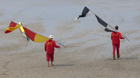 охранять : Life guard or Rescue teams on the beach are flagged down on the sand. Стоковые видеозаписи
