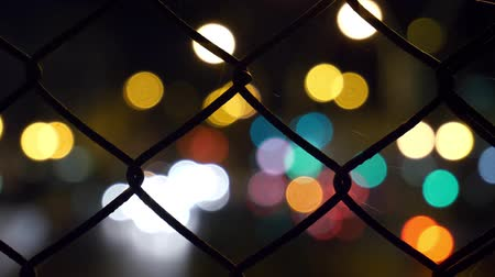 profundidade de campo rasa : Bokeh Circles Of Street Traffic Behind Metal Mesh Fence. Motion Background. Stock Footage