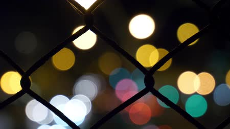 малая глубина резкости : Bokeh Circles Of Street Traffic Behind Metal Mesh Fence. Motion Background. Стоковые видеозаписи