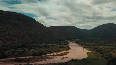rosário : A Bridge Through River On A Mountain Valley Stock Footage