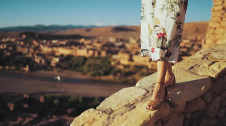 adam : a woman carefully walking on a concrete ledge. Morocco