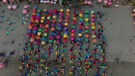 fasola : Parasols in rainbow colors and bean bag chairs on empty white sandy beach.