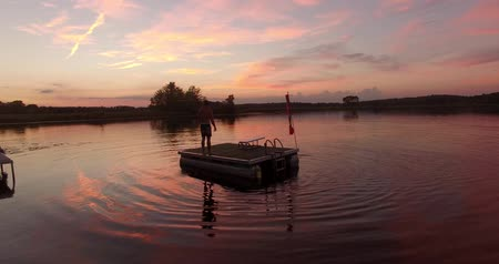 desperto : a man diving and swimming into a lake during a late evening sunset Stock Footage