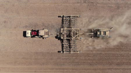 plough land : Aerial Footage Of A Modern Tractor Plowing Dry Field Stock Footage