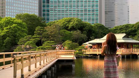 sado : Young girl takes pictures in the Hamarukyu garden. Stock Footage