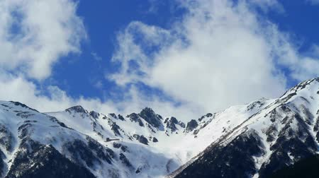 ridge line : Time lapse of blue sky with cool clouds over snow capped mountains. Stock Footage