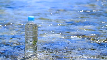 tisztaság : Pet bottle of pure drink with clean blue water stream in background.
