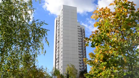 bloklar : High-rise apartment building surrounded by an autumnal trees Stok Video
