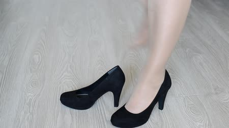 süet : Woman takes off down a black high-heeled shoes